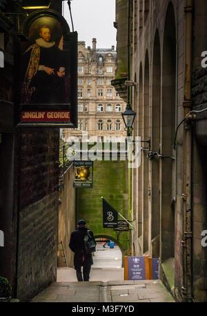 Man walking in Fleshmarket Close alley with Jinglin Geordie and Halfway House pub signs, Edinburgh, Scotland, UK - Stock Photo