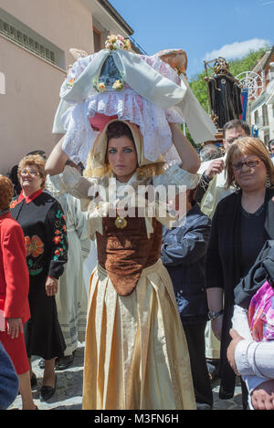 During the procession the girls of Cocullo, dressed in traditional clothes, carry on their heads wicker baskets - Stock Photo