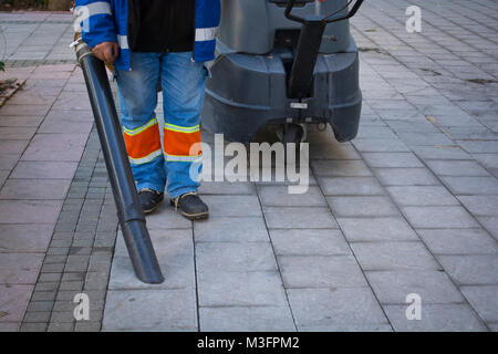 street cleaner walking in central city with industrial - Stock Photo