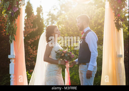Just married woman and man kiss each other in summer green nature background during wedding ceremony - Stock Photo