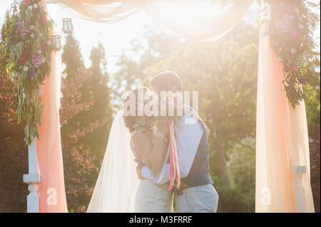 Just married woman and man kiss each other in summer green nature background during wedding ceremony. Happy just - Stock Photo