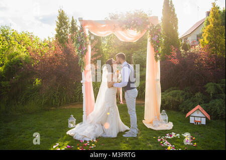 Just married woman and man kiss each other in summer green nature background during wedding ceremony. Soft sunset - Stock Photo