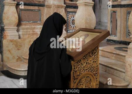 Eastern Orthodox nun prays in front of a religious icon inside the Katholikon or Catholicon Chapel in the Church - Stock Photo