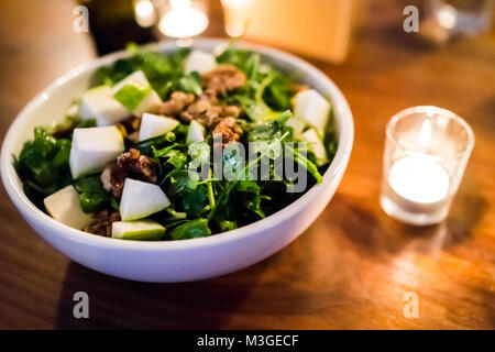 Macro closeup of arugula apple green vegan vegetarian salad in restaurant with candied nuts, walnuts, on wooden - Stock Photo