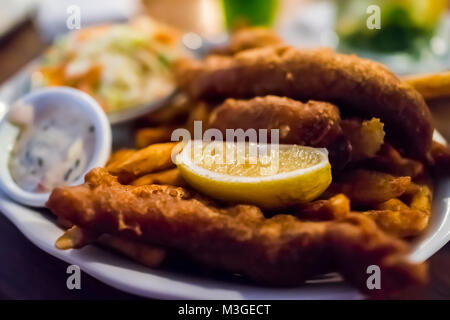 Macro closeup of deep fried fish and chips battered filets brown golden crust in restaurant with lemon slice, tartar sauce, side dish on table in even