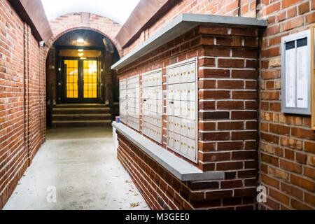 Brick apartment building entrance in downtown NYC New York City with mailbox post mail boxes, empty corridor in - Stock Photo
