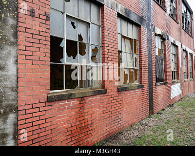 Exterior of abandoned brick building with broken windows in Montgomery Alabama, USA. - Stock Photo