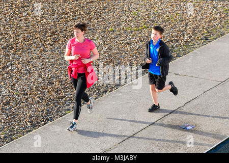Lyme Regis, Dorset, UK.  11th February 2018.  UK Weather.  Joggers on the seafront enjoying the clear skies on a - Stock Photo