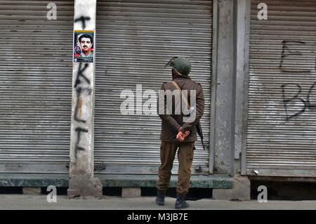Srinagar, India. 11th Feb, 2018. An Indian policeman looks on a poster with portrait of the Maqbool Bhat during - Stock Photo