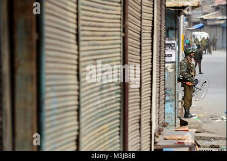 Srinagar, India. 11th Feb, 2018. An Indian Paramilitary soldier stands guard during restrictions in old city of - Stock Photo