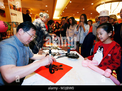 Los Angeles, USA. 10th Feb, 2018. An artist writes Chinese? character 'Fu' which means luck for a girl at Millennium - Stock Photo