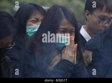 Hong Kong, CHINA. 11th Feb, 2018. Woman weeps as she offer prayer to her beloved during traditional ceremony held - Stock Photo