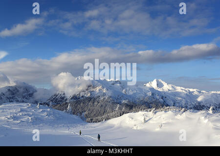 Mother and son hiking on snow covered mountain with pine trees and high mountains for the background. - Stock Photo
