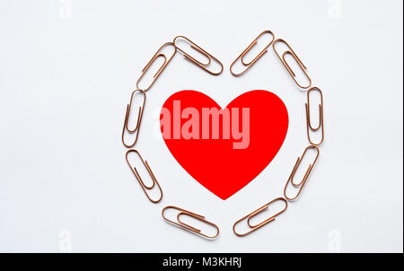 Red heart in heart shape paperclip on white background, love and romance - Stock Photo