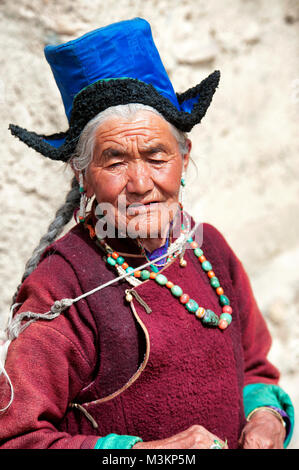 Elderly woman on pilgrimage at gompa, Ladakh. Dressing traditional clothing: a robe called Kuntop. On backs a colorful - Stock Photo