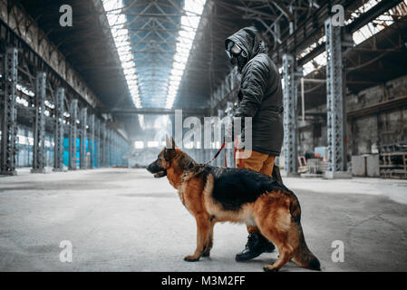 Stalker soldier in gas mask and dog in abandoned building, survivors after nuclear war. Post apocalyptic world. - Stock Photo