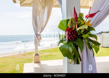Wedding setup - wedding pergola decorated with white fabric curtains and tropical flowers, Bali, Indonesia - Stock Photo
