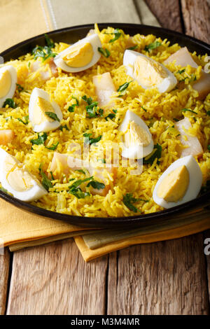 traditional food: Kedgeree rice with smoked fish, eggs, greens and spices close-up on a plate. vertical - Stock Photo
