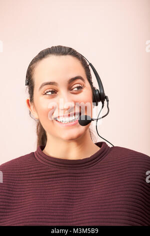 Cheerful woman using headset working in call center in a concept of a call center operator, customer service or - Stock Photo
