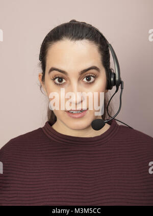 Call center operator with a surprised expression listening to a conversation on her headset and staring wide eyed - Stock Photo