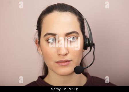 Studio shot close-up portrait of a young woman thinking while listening to a single headphone with microphone during - Stock Photo