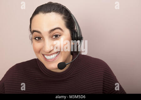 Attractive friendly young woman wearing a headset and smiling at the camera in a concept of customer services, call - Stock Photo