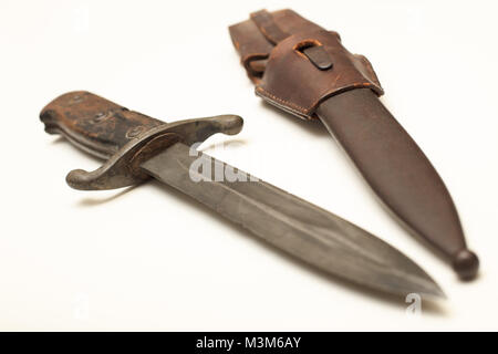 Old dagger with a worn leather sheath to carry the weapon isolated on a white background with copy space - Stock Photo