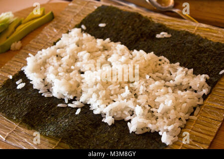 Nori algae leaf with rice for rolls with cucumber and avocado on wooden board - Stock Photo