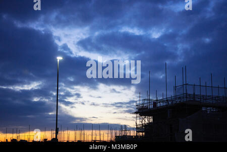 Sunset on a building site in silhouette  and a street light - Stock Photo