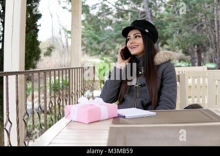 girl talking on the phone in the street restaurant - Stock Photo