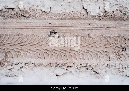 Dirty traces of the tread on white snow-covered road. In the winter traces of snow from the car. - Stock Photo