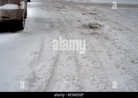 The car is on the roadside in winter, tracks of the wheels on the snow, in the winter in the city. - Stock Photo
