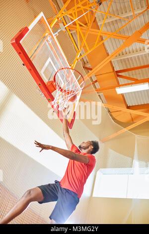 Basketball player making slam dunk - Stock Photo