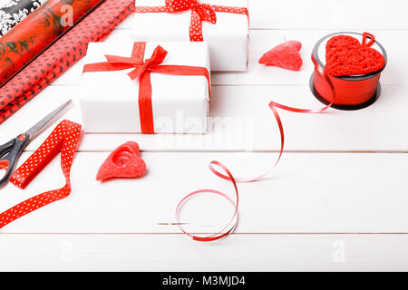 Gift boxes wrapped in white paper and red ribbons, hearts, candles, and a working surface for festive gift packing - Stock Photo