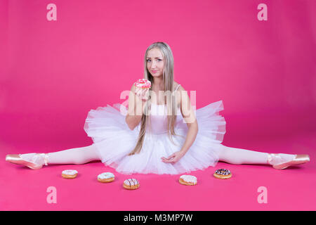 Pretty blonde ballerina in tutu skirt doing a split and eating a donut on pink backdrop. - Stock Photo