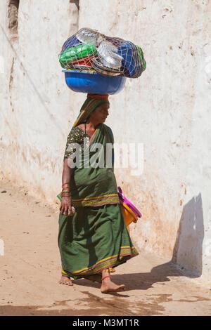 India, Karnataka, Badami, woman carrying a basket with pots on her head - Stock Photo