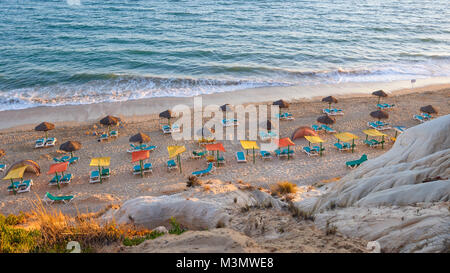 Sunbeds and umbrellas on the Falesia Beach in afternoon sun, Algarve, Portugal - Stock Photo