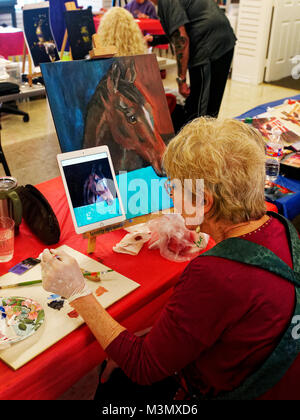 Seniors having lived a long hard still stay active expressing themselves in painting class, Pam Smith uses a photo - Stock Photo