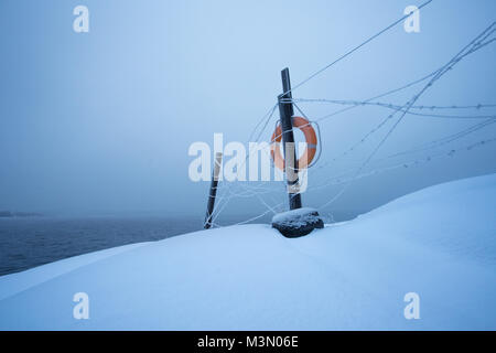 Simplistic view of barbed wire fence with life buoy against foggy sea at winter - Stock Photo
