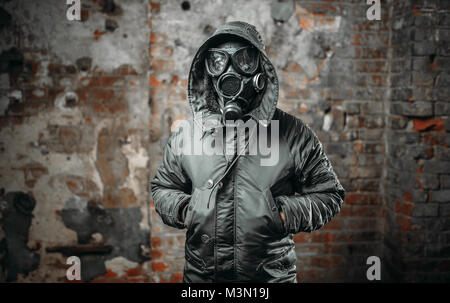 Stalker soldier in gas mask, survivor man after nuclear war. Post apocalyptic lifestyle, doomsday, horror of radiation - Stock Photo