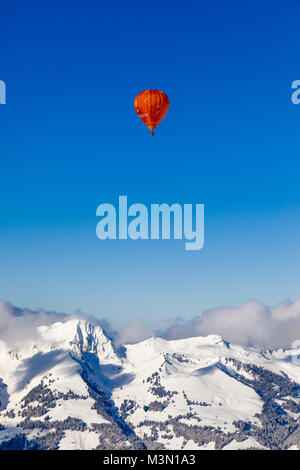 40th International Hot Air Balloon Festival in Château-d´Oex - balloons are flying in the blue sky over the swiss - Stock Photo