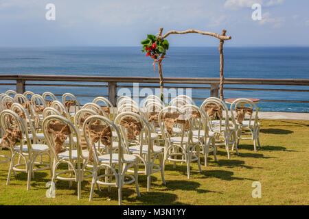 Wedding arch for a ceremony decorated with tropical flowers, and white chairs on the cliff edge of the ocean. - Stock Photo