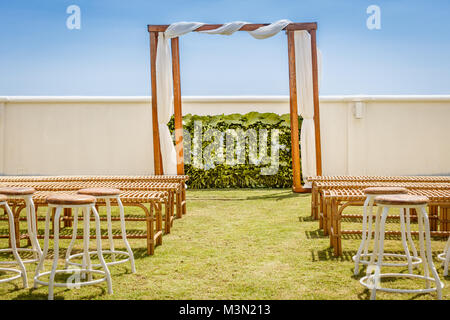 Wooden wedding arch for a ceremony decorated with white fabric, flower wall with word LOVE made with tropical flowers, - Stock Photo