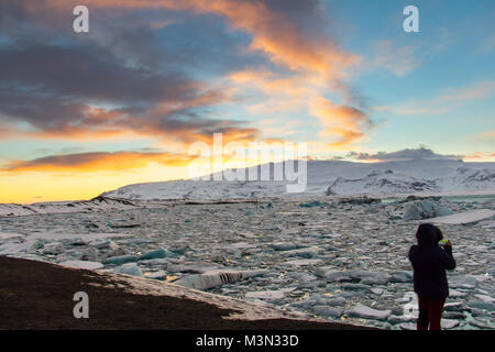 A woman in silhouette is phototraphing Glacier Lagoon (Jokulsarlon) at sunset with her mobile phone on the south - Stock Photo
