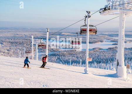 Skiers on the piste at The ski resort of Ruka in Finland - Stock Photo