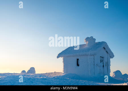 A snow encrusted cabin on the summit of a hill in Finland - Stock Photo