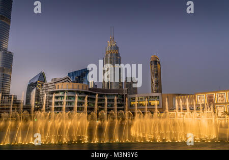 Dubai, UAE - Jan 9, 2018. Evening view of Dubai Fountain's dancing waters performance accompanied by colorful syncing - Stock Photo