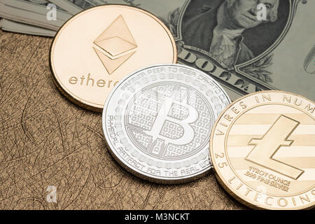 cryptocurrency Silver and gold Bitcoin,litecoin,ethereum on dollar banknote on golden table,Virtual Digital money - Stock Photo