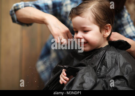 A little boy is trimmed in the hairdresser's bright emotions on  - Stock Photo