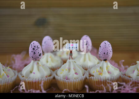 Easter time with cupcakes topped with miniature person figurine holding a sign for I love Easter - Stock Photo